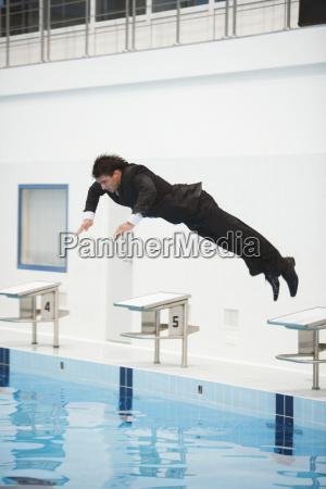 empresario saltando en la piscina