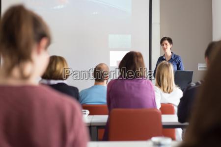 mujer dando presentacion en sala de