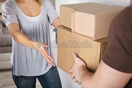 repartidor dando paquete de caja a