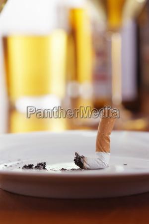 cigarrillo en cenicero sobre mesa con