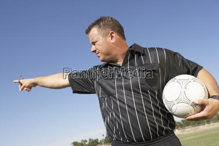 Arbitro con balon de futbol apuntando