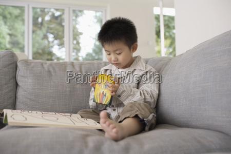 ninyo con libro para colorear sentado