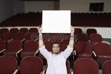 estudiante masculino levantando tablero de la