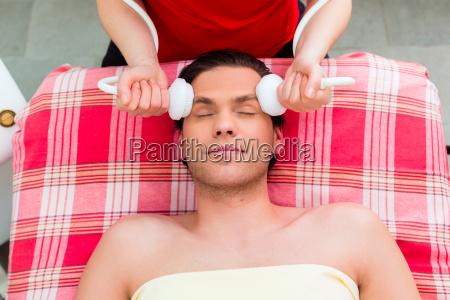 man having face massage in wellness