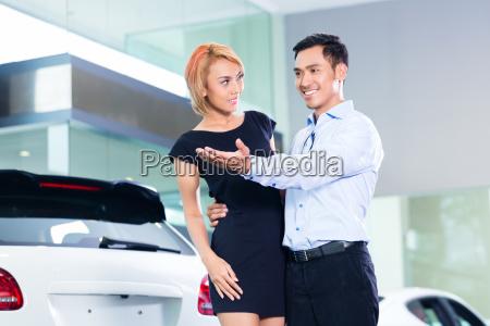 asian couple choosing luxury suv car
