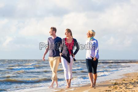 friends enjoying sunset at ocean beach