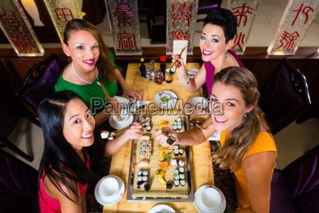 young people eating sushi in asian