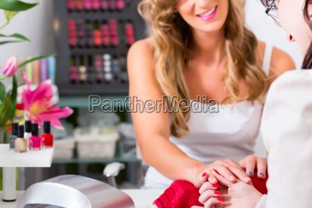 mujer recibiendo manicura en salon de