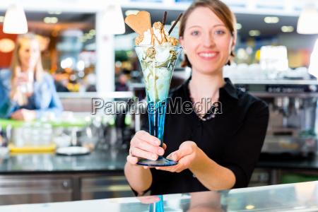 vendedora en heladeria presentando helado