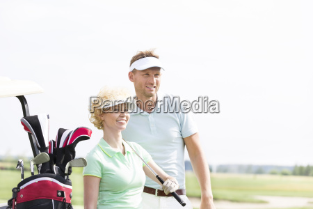 smiling golfers standing at golf course