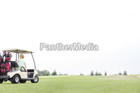 couple sitting in golf cart against