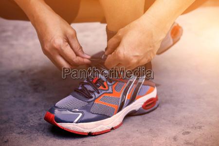manos atando zapatos para correr