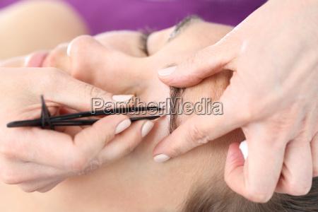 pinzas de ceja depilacion ajustando las