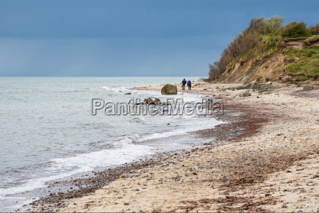walkers on the coast of the