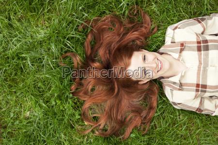 adolescente acostado en la hierba