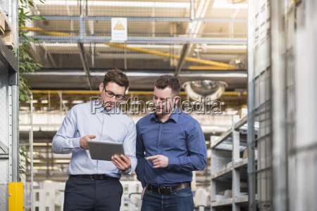 dos hombres con tableta hablando en