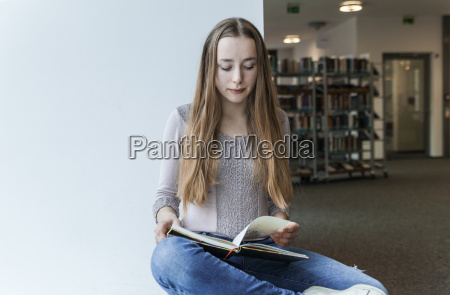 teenage girl reading book in a