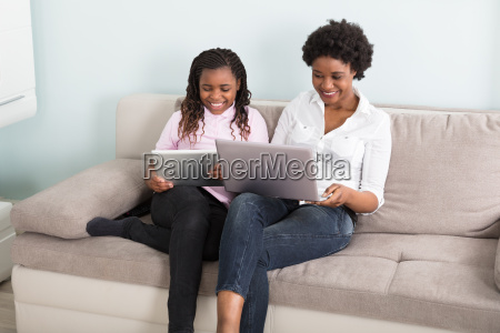 mother and daughter using laptop and