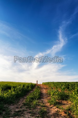 lone woman standing on a dirt