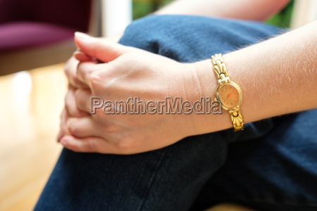 folded hands and arm with gold