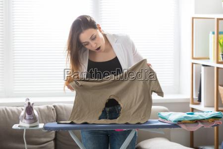 woman looking at burnt t shirt