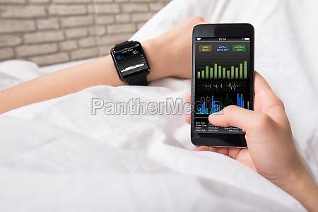 manos con telefono inteligente y reloj