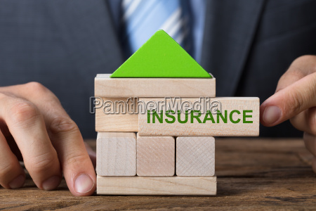 businessman building house with insurance block