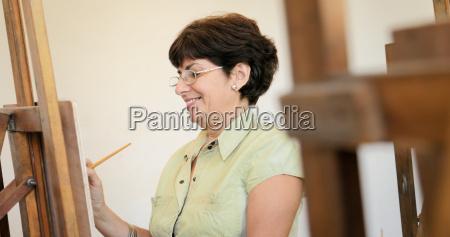 mujer senior aprendiendo a pintar en