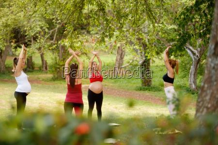 mujeres embarazadas haciendo yoga con entrenador