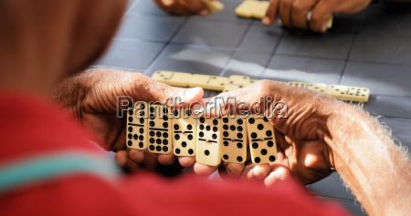 negro retirado hombre mayor jugando domino
