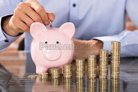 empresario insertar monedas en piggy bank