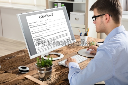 businessman looking at contract on computer
