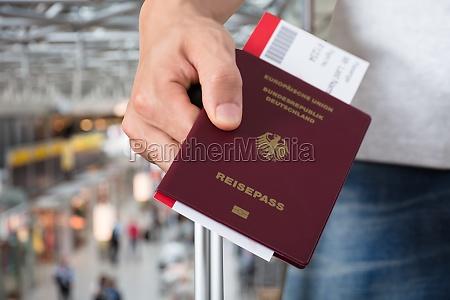 persona con equipaje sosteniendo pasaporte y