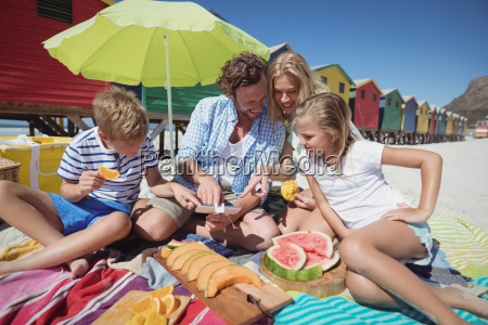 happy family sitting together by fruits