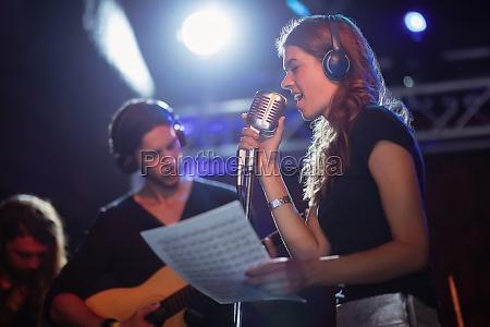 cantante llevando auriculares mientras canta en