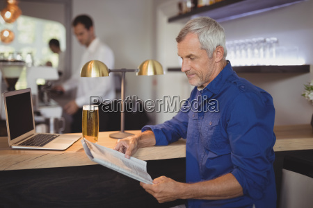 mature man reading newspaper at counter