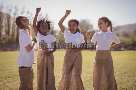 happy schoolgirls standing in sack during