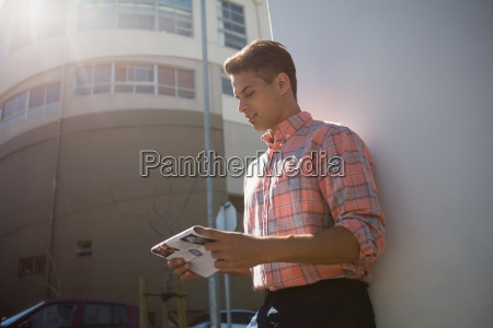 man reading paper while standing by