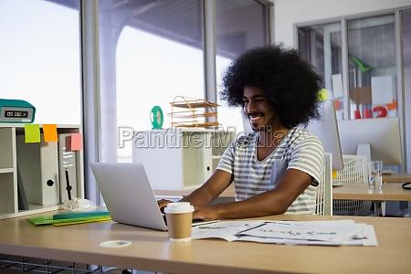 smiling man using laptop at office