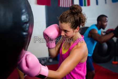 young female boxer punching bag