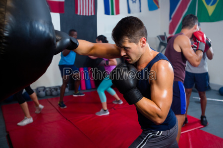 young male boxer punching bag