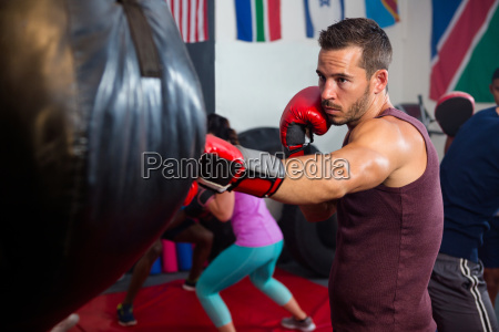 young male boxer punching black bag