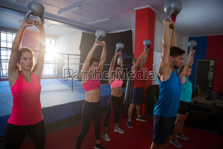 young athletes lifting kettles against boxing