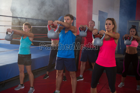 young athletes exercising with kettles by