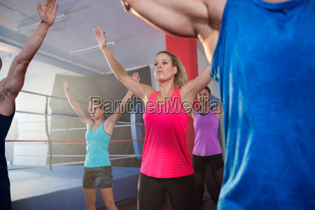 athletes exercising with arms raised by