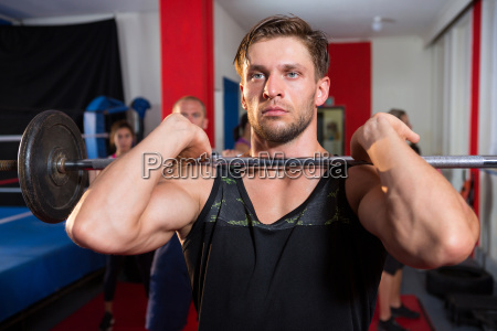 young male athlete lifting barbell by