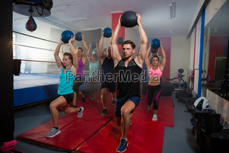 athletes practicing lunge with exercise ball
