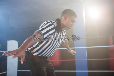 young male referee showing hand sign