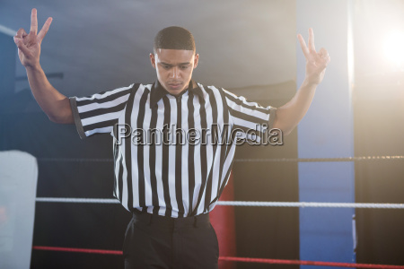 young male referee gesturing while looking