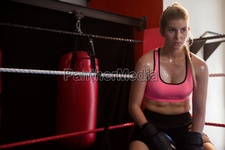 thoughtful woman sitting in boxing ring